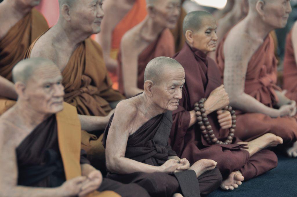 monjes sentados en el piso mientras rezan