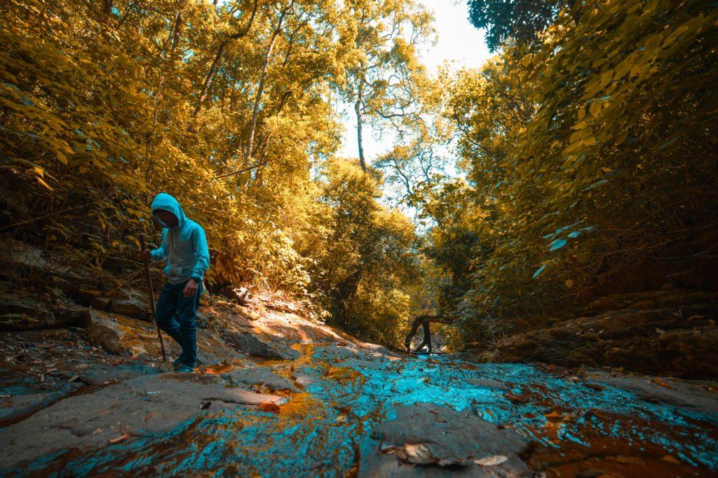 Persona practicando trekking a lado de un río