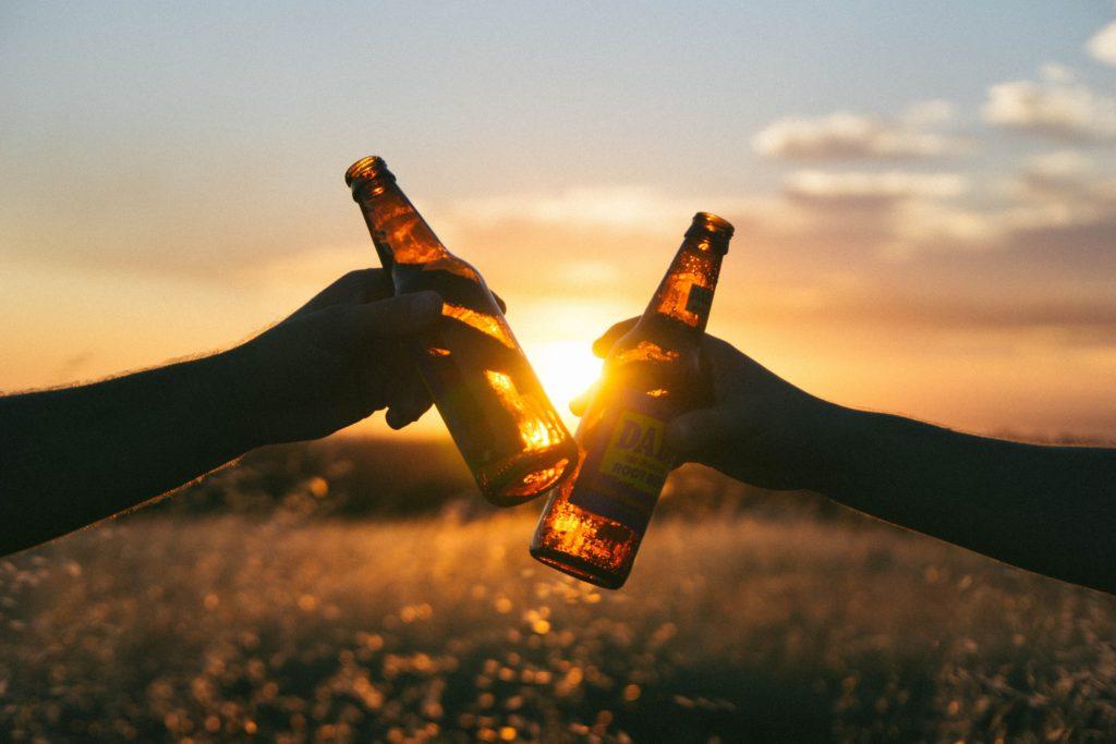Brindis con cerveza en atardecer